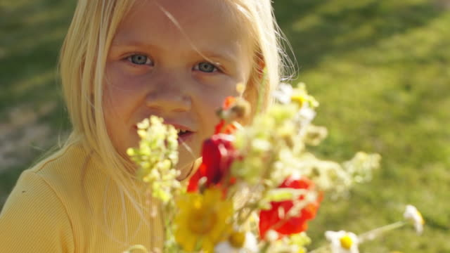 Portrait of one child with bunch of wild flowers in park.