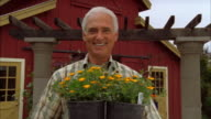 CU, Portrait of plant nursery employee holding potted flowers and smiling, Cambria, California, USA