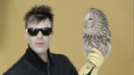 Portrait of punk man sticking tongue out with Owl perched on hand, with falconer's glove on