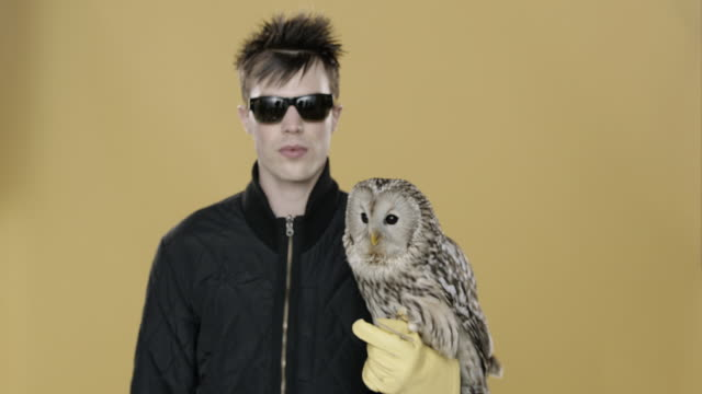 Portrait of punk man with Owl perched on hand coming in close to camera