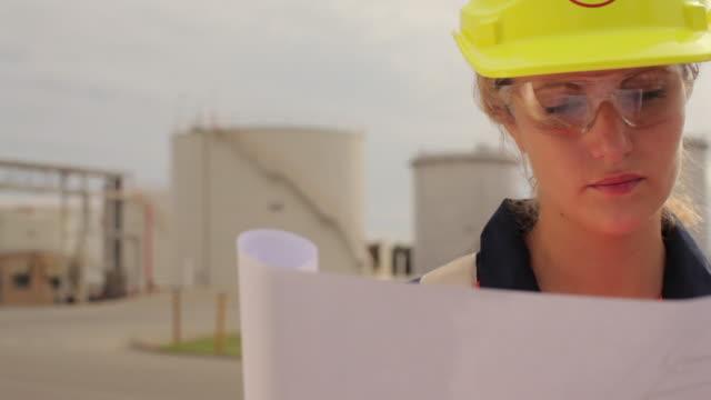 CU TU Portrait of refinery worker looking at blueprints / Perth, Australia