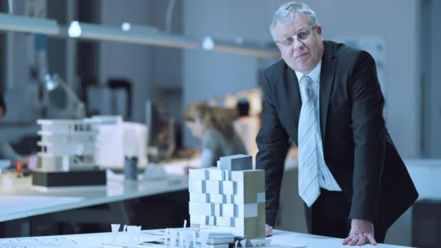 DS Portrait of senior business man with building model
