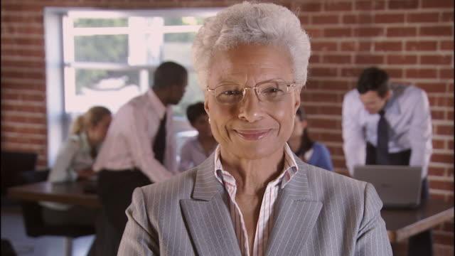 CU, SELECTIVE FOCUS, Portrait of senior businesswoman, colleagues in background, Los Angeles, California, USA
