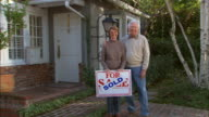 ZO, MS, Portrait of senior couple in front of house with  For Sale sign, Los Angeles, California, USA