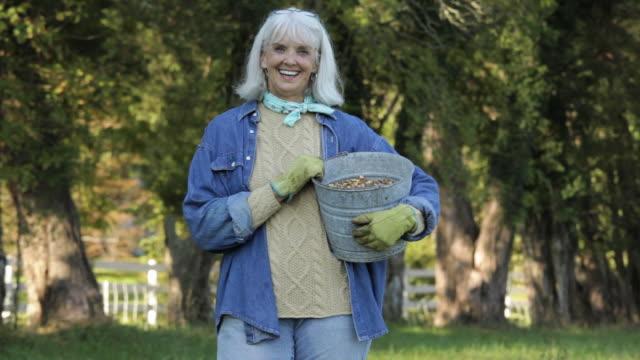 Portrait of Senior Farmer Holding Bucket of Animal Feed in Pasture / Richmond. Virginia, USA