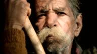Ritratto di uomo anziano con i baffi con grandi bastone in bambù.