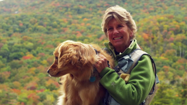 MS Portrait of senior woman sitting and patting Golden Retriever dog outdoors, Manchester, Vermont, USA