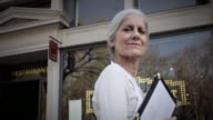 MS LA Portrait of senior woman smiling, holding menus, standing outside restaurant