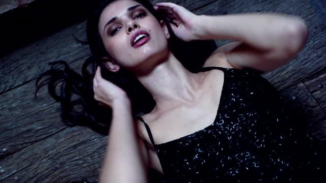 CU Portrait of sensuous young woman lying on wooden floor