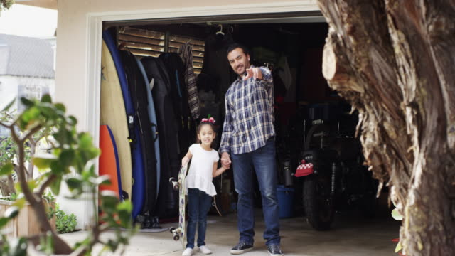 Portrait of single dad and daughter in front of garage