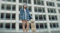 WS. Portrait of skater girl standing with skateboard in urban skatepark.