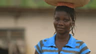 Portrait of smiling african woman carrying water on her head