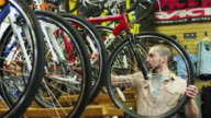 MS ZI CU Portrait of smiling bike shop employee holding mountain bike  / Portland, Oregon, USA