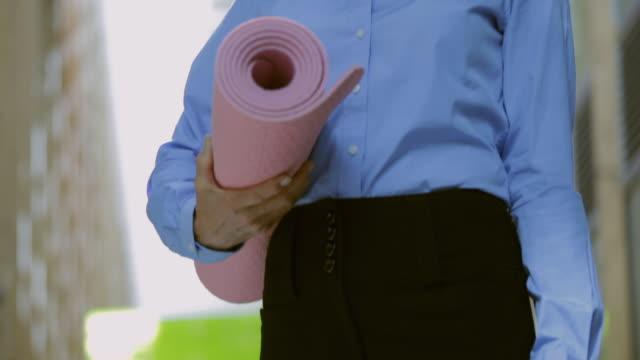 CU TU Portrait of smiling businesswoman holding yoga mat / Vancouver, British Columbia, Canada
