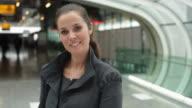 CU Portrait of smiling businesswoman in airport terminal / Toulouse, Haute-Garonne, France