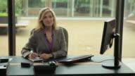 MS Portrait of smiling businesswoman working at desk / Portland, Oregon, USA