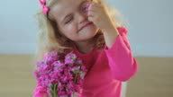 MS Portrait of smiling girl (4-5) playing with pink Matthiola flowers / Jersey City, New Jersey, USA
