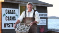 MS Portrait of Smiling Waterman Holding Basket of Fresh Oysters in Front of Seafood Shack / Oyster, Virginia, USA