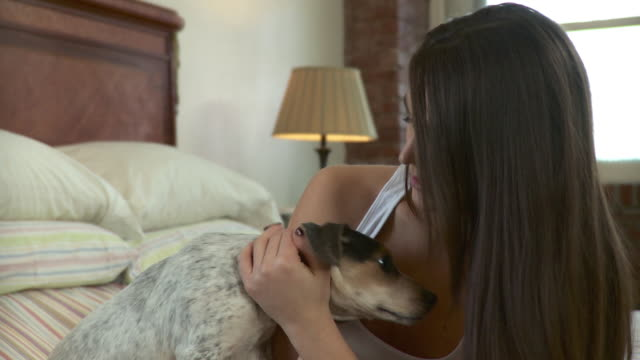 CU Portrait of smiling young woman with dog licking her face in bedroom / Brooklyn, New York City, New York, USA