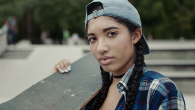 MS SLO MO. Portrait of teenage girl holding skateboard in skatepark.