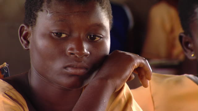 CU Portrait of teenage girl sitting in classroom, Tamale, Ghana