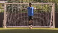 WS Portrait of teenage (16-17) soccer player balancing on ball, London, UK