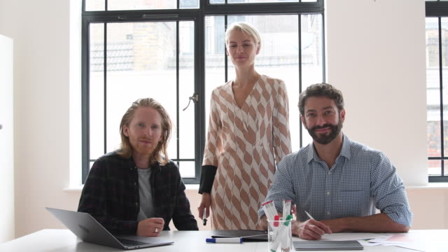 Portrait of three business colleagues in modern office smiling towards camera