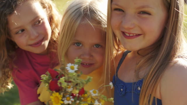 Portrait of three children with bunch of wild flowers in park.