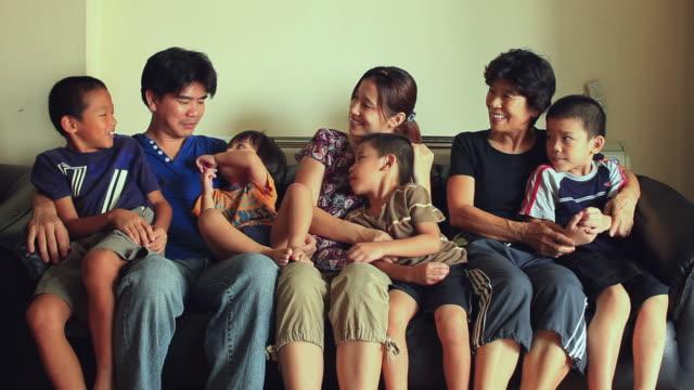 MS Portrait of three generation family with four sons (8-9, 6-7,4-5, 2-3) sitting on sofa / Watthana, Bangkok, Thailand