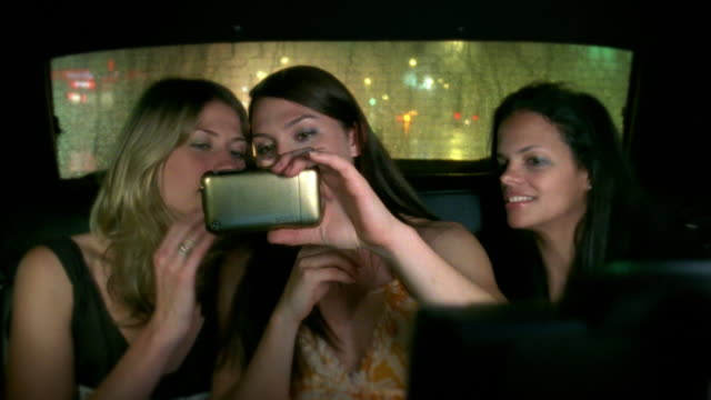 MS Portrait of three young women applying make-up laughing in back of cab, New York City, New York, USA
