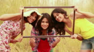 Portrait of three young women looking through from a frame, Delhi, India