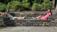 WS Portrait of twin sisters (12-13) on stone bench in garden, Chapel Hill, North Carolina, USA