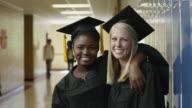 MS ZI Portrait of two female graduates (16-17) in school corridor / Spanish Fork City, Utah, USA