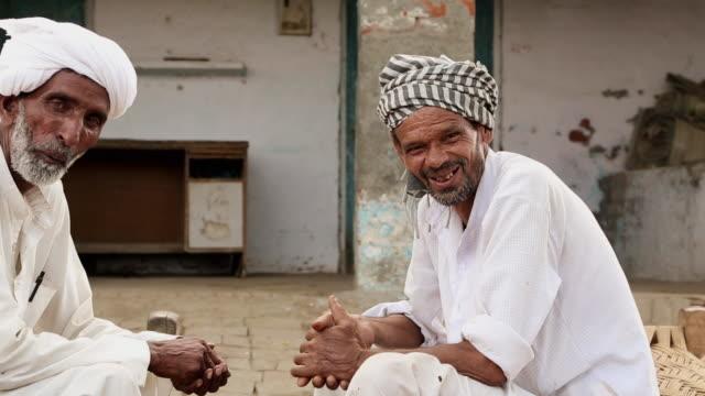 Portrait of two senior men smiling, Haryana, India