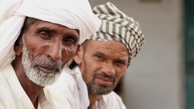 Portrait of two senior men talking, Haryana, India