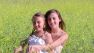 MS Portrait of two sisters sitting and smiling in beautiful mustard field / Thousand Oaks, California, United States