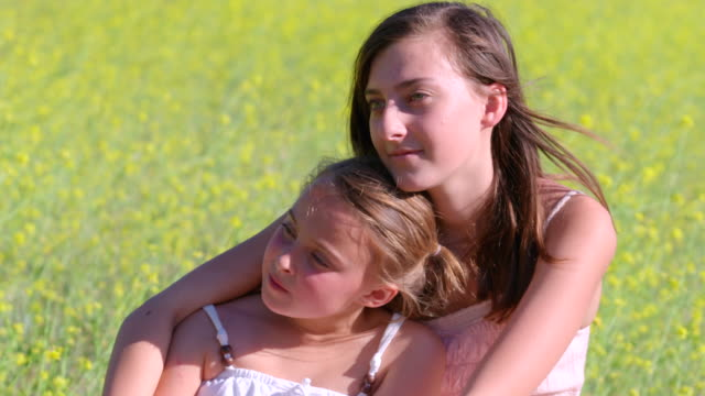 CU Portrait of two sisters sitting in beautiful mustard field looking into distance pensively / Thousand Oaks, California, United States