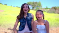 MS SLO MO Portrait of two sisters sitting in mustard field with laughing hard / Thousand Oaks, California, United States