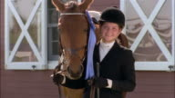 Portrait of winner of equestrian competition posing with horse wearing blue ribbon