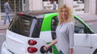 SLO MO Portrait of woman plugging car at EV station