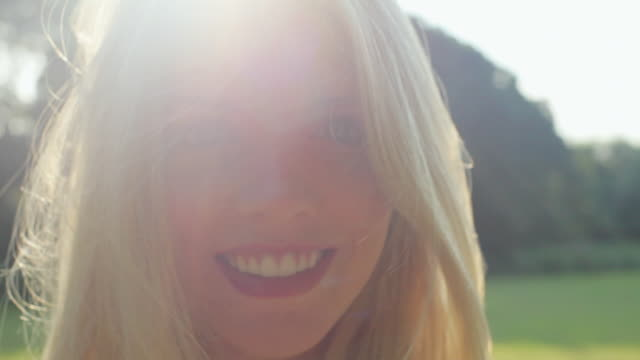 CU Portrait of young blond woman with wind blowing in her hair / London, United Kingdom