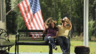 WS Portrait of young couple in porch greeting with cowboy hats by American flag / Madison, Florida, USA