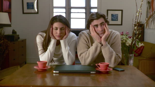 MS Portrait of young couple sitting at dining table with heads in hands in front of closed laptop and tea cups / Brooklyn, New York City, New York, USA