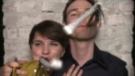 CU Portrait of young couple smiling and blowing party whistle against brick wall, New York City, New York, USA