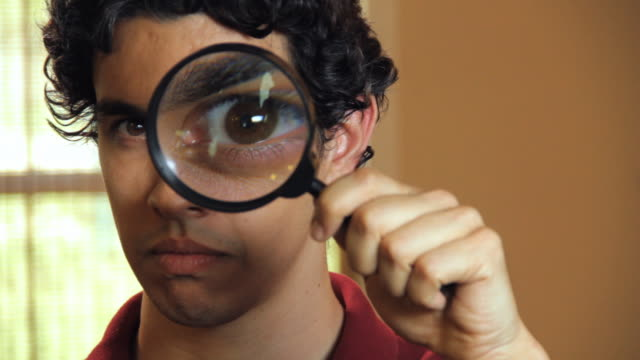 CU Portrait of young man looking through magnifying glass and smiling / Madison, Florida, USA