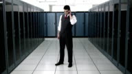 WS CU Portrait of young man talking on mobile phone in server room