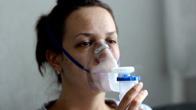 portrait of young woman doing inhalation at home
