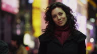 CU Portrait of young woman in Times Square at night / New York City, New York State, USA