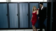 DS MS Portrait of young woman leading man by tie in server room