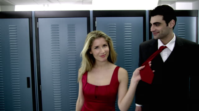 DS CU Portrait of young woman leading man by tie in server room